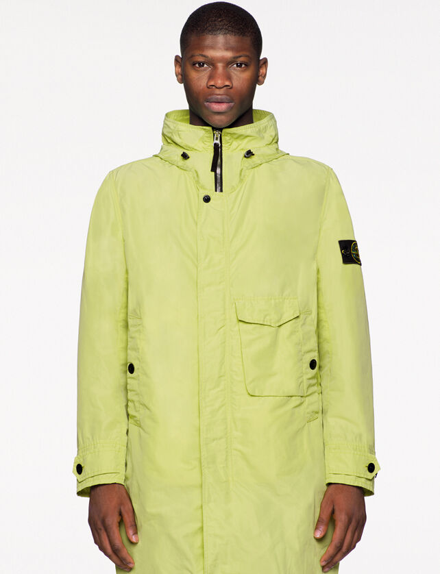 Model wearing a long yellow jacket with standing collar, a zipper fastening hidden by flap with snap, two vertical hand pockets with snap and one patch pocket with flap.