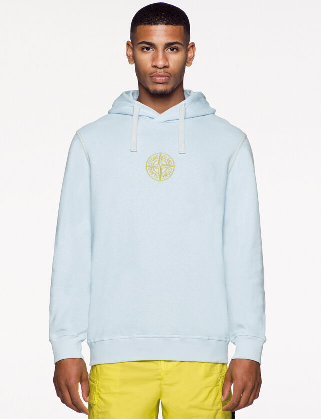 Model wearing yellow pants and a light blue sweatshirt with hood, and the Stone Island compass rose logo embroidered on the chest.