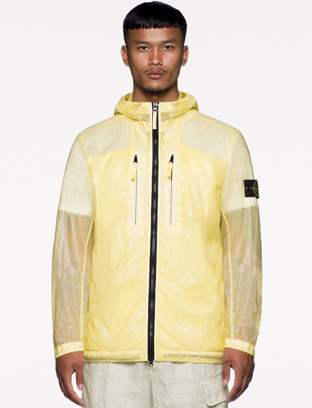 Model wearing off white pants and a yellow see through hooded jacket with shiny effect, two way zipper fastening, two vertical chest pockets with zipper and the Stone Island badge on the upper left arm.