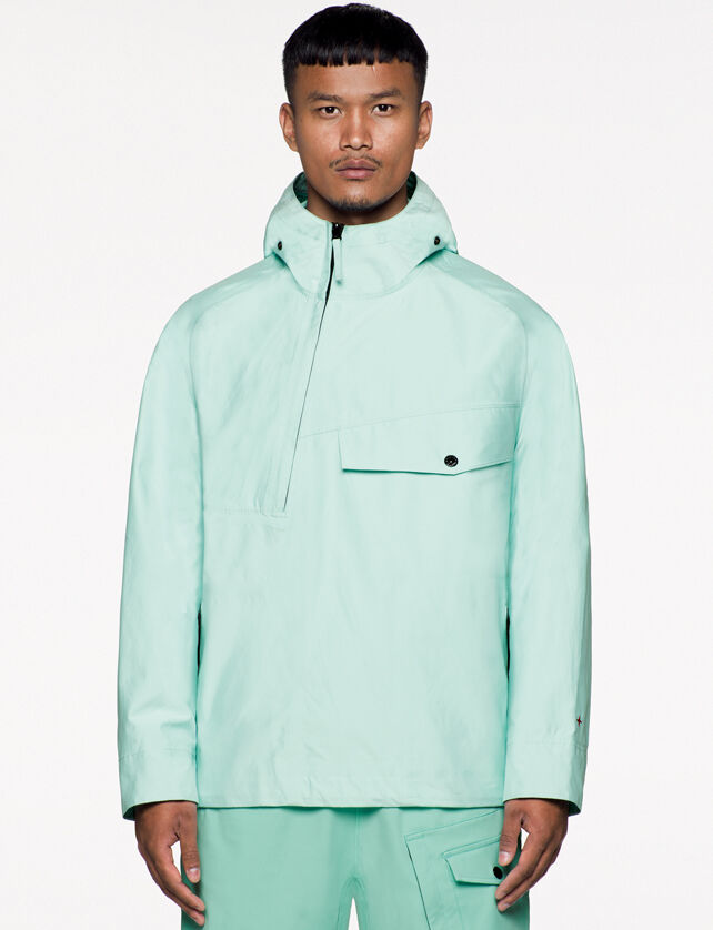 Model wearing mint green cargo pants and a matching jacket with hood, an asymmetrical half zipper fastening, a chest pocket with flap and snap and the Stone Island little star in red on the left cuff.