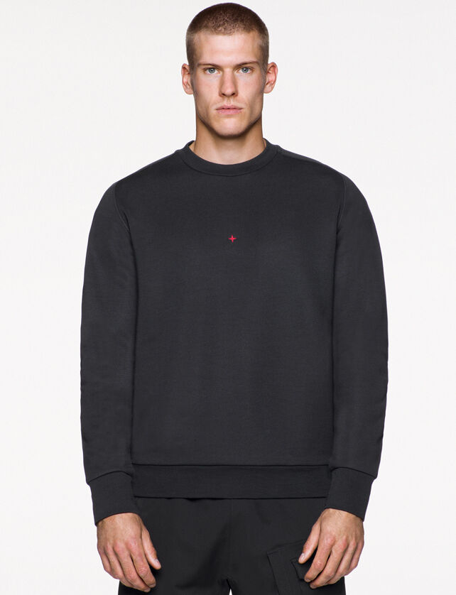 Model wearing dark colored pants and a matching sweatshirt with round neck and the embroidery of the Stone Island little star in red on the chest.