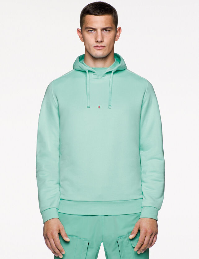 Model wearing mint green cargo pants and a matching sweatshirt with hood and the embroidery of the Stone Island little star in red on the chest.