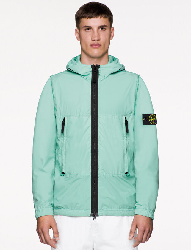Model wearing white pants and a mint green hooded jacket with black zipper fastening, two vertical hand pockets with zipper and the Stone Island badge on the upper left arm.
