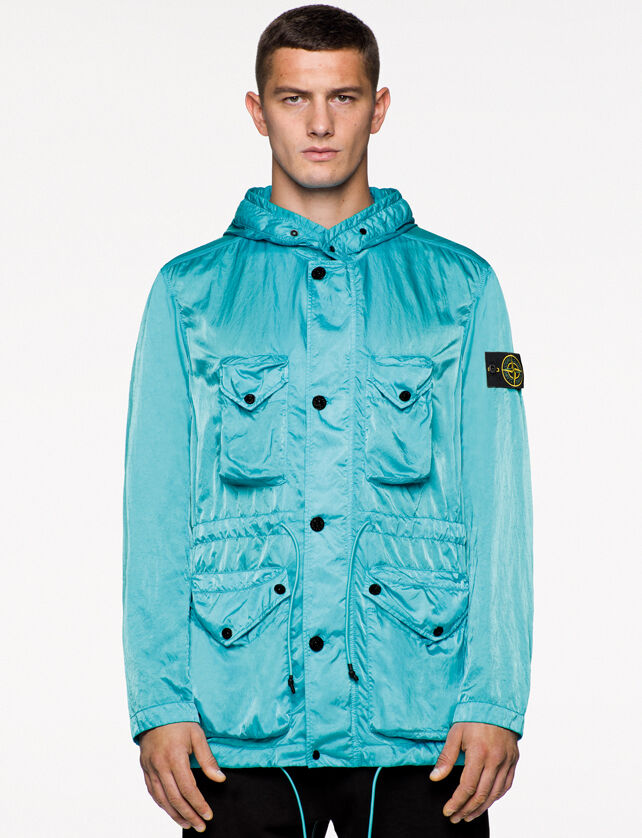 Model wearing black pants, a light blue shiny effect jacket with hood, button fastening, two bellows chest patch pockets with a triangular flap and snap, drawstring at waist and two patch hand pockets with flap and button fastenings.
