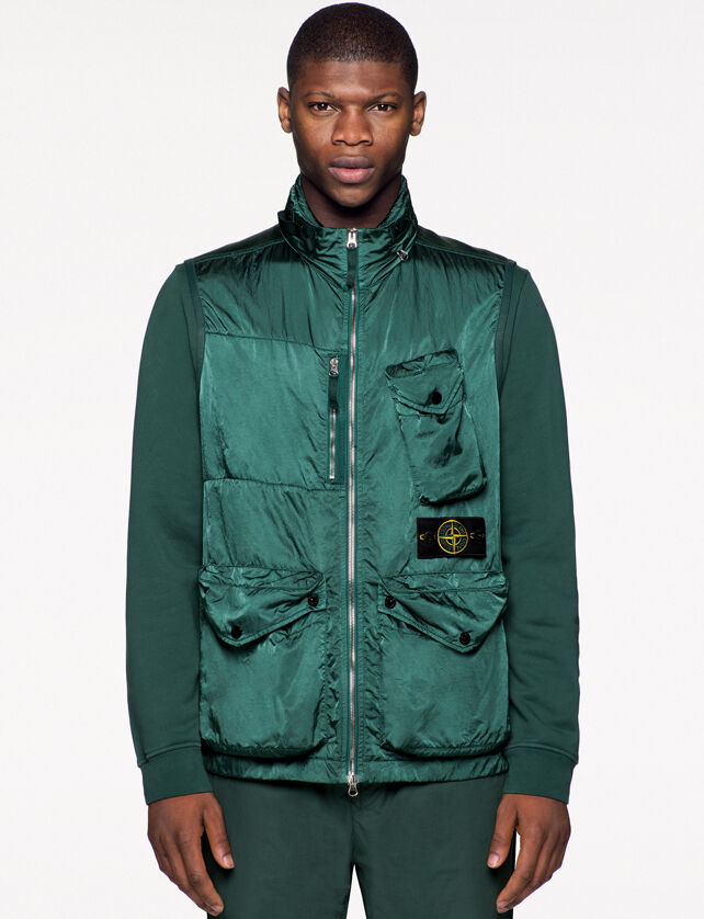Model wearing dark green pants, a matching sweatshirt and a green shiny effect vest with standing collar, two way zipper fastening, one bellows chest patch pocket on the left side with a triangular flap and snap, one vertical chest pocket with zipper, the