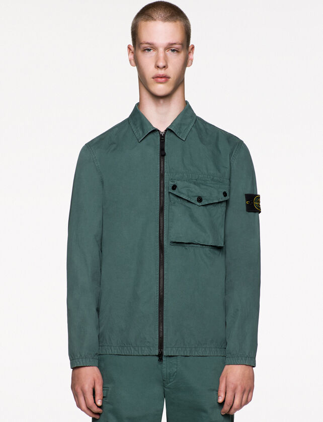 Model wearing dark green pants and a matching overshirt with two way zipper fastening, a bellows pocket with flap and snaps on the chest and the Stone Island badge on the upper left arm.