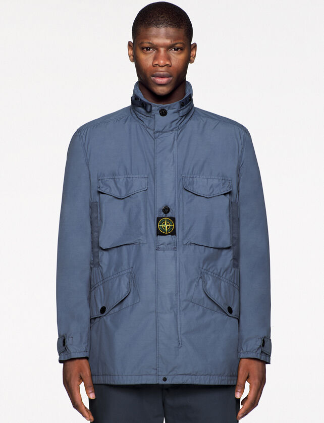Model wearing dark colored pants and a gray blue field jacket with standing collar with strap, button fastening placket with a buttoned central strap on the chest featuring the Stone Island badge, patch chest pockets with flap and two hand pockets with sl