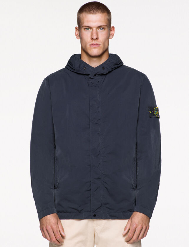 Model wearing off white pants and a dark blue jacket with hood and snaps, hidden fastening, two standing hand pockets and the Stone Island badge on the upper left arm.