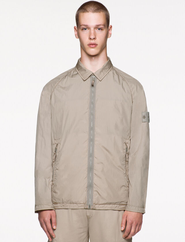Model wearing beige pants and a matching jacket with shirt collar, zipper fastening, two slanting hand pockets with zipper fastening, raglan sleeves and the Stone Island ghost badge on the upper left arm.