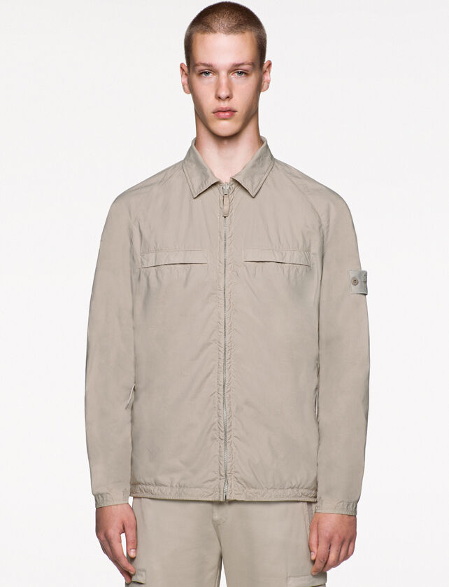 Model wearing beige cargo pants and a matching jacket with shirt collar, zipper fastening, two slit pockets on the chest with hidden entrance, raglan sleeves and the Stone Island ghost badge on the upper left arm.