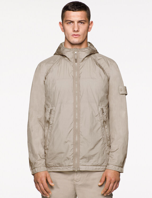 Model wearing beige pants and a matching hooded jacket with zipper fastening, two slanting hand pockets with zipper, raglan sleeves and the Stone Island ghost badge on the upper left arm.