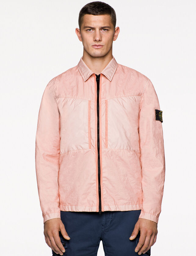 Model wearing dark blue pants and a light pink jacket with shirt collar, two way zipper fastening and the Stone Island badge on the upper left arm.
