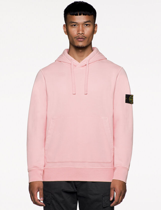 Model wearing dark colored cargo pants and a light pink hooded sweatshirt with contour drawstring on hood, slanting hand pockets and the Stone Island badge on the upper left arm.