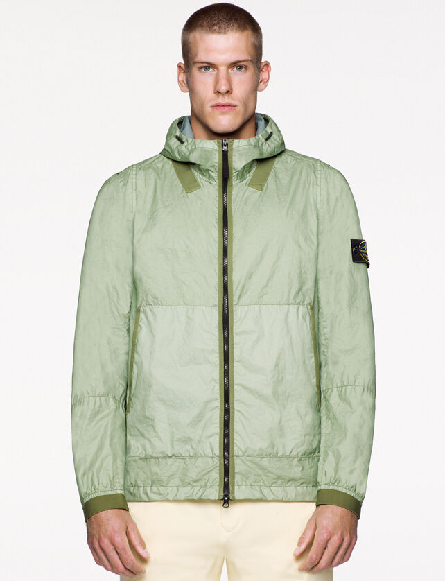 Model wearing off white pants and a light green jacket with darker green edging details, hood with drawstring, two way zipper fastening and the Stone Island badge on the upper left arm.