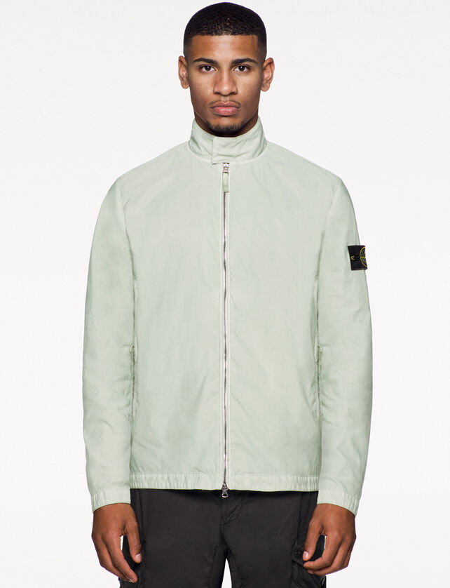 Model wearing black pants and a light sage green jacket with standing collar with flap, two way zipper fastening and the Stone Island badge on the upper left arm.
