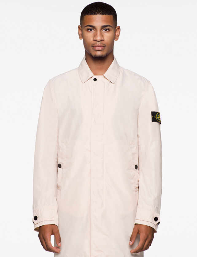 Model wearing an off white trench coat with a collar with snap, hidden fastening, slanting hand pockets with snap, straps with buttons at cuffs and the Stone Island badge on the upper left arm.