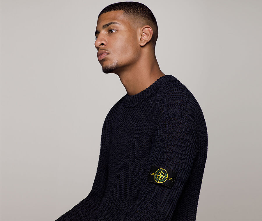 Close up shot of model wearing a dark colored sweater with a ribbed crewneck, and the Stone Island badge on the upper left sleeve.