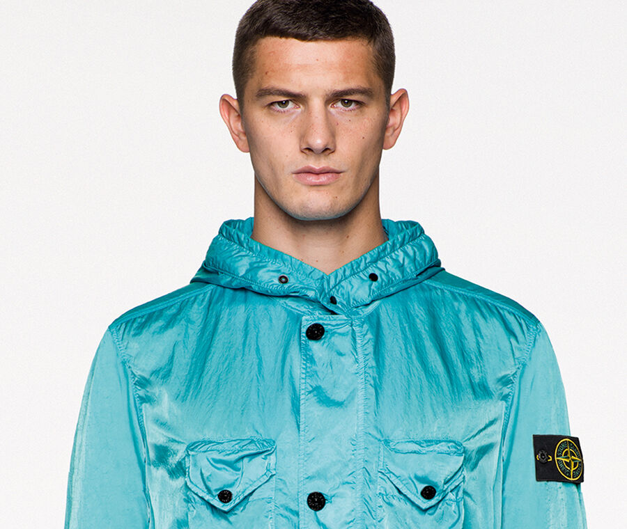 Model wearing black pants with a light blue Stone Island compass rose logo and a light blue jacket with button fastening, drawstring at the waist and bottom hem, two bellows chest pockets and two bellows hand pockets, all with flap and snap fastening.