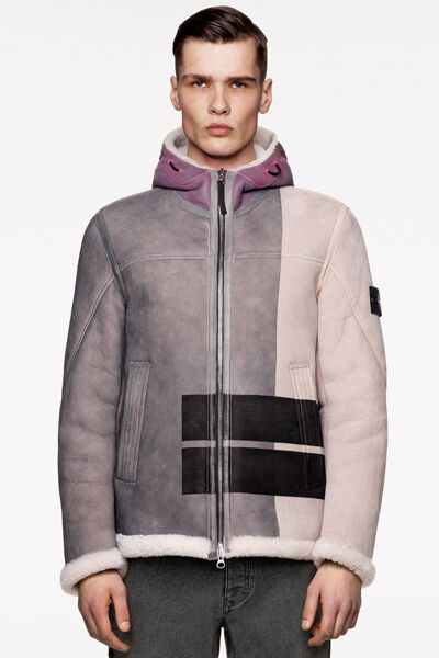 Model wearing burgundy check and paint splatter print pants and a matching anorak with standing collar, front hand pockets with flap and central buttoned strap bearing the Stone Island badge.