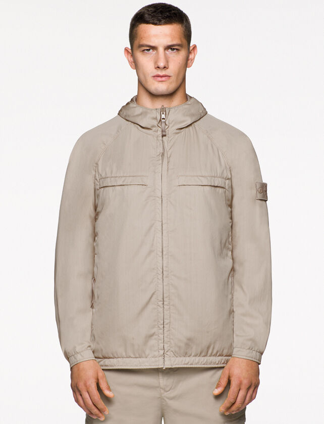 Model wearing beige pants and a matching jacket with hood, zipper fastening, two slit pockets on the chest with hidden entrance, raglan sleeves and the Stone Island ghost badge on the upper left arm.