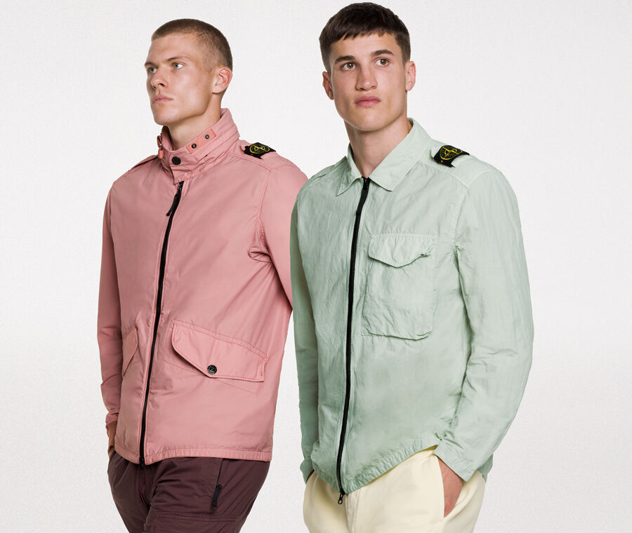 Two models wearing the same outfit, consisting of dark green shorts and a matching overshirt with two way zipper fastening, a bellows pocket with flap and snaps on the chest and the Stone Island badge on the upper left arm.