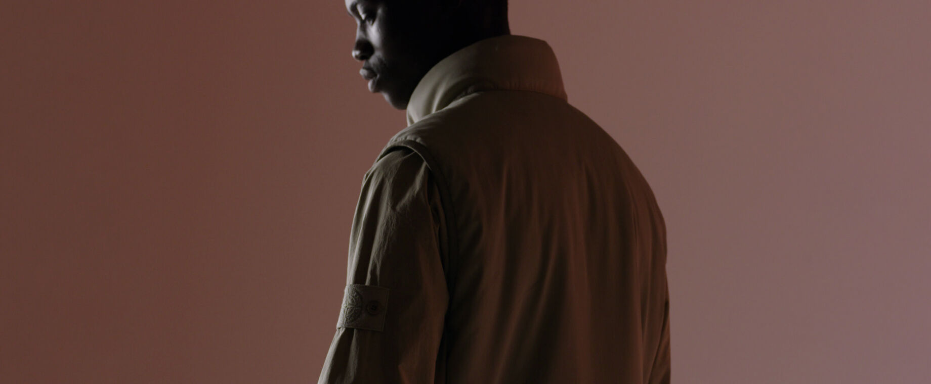 Close up shot of model in dim light, wearing a beige vest with standing collar over a top with the Stone Island ghost badge on the upper left arm.