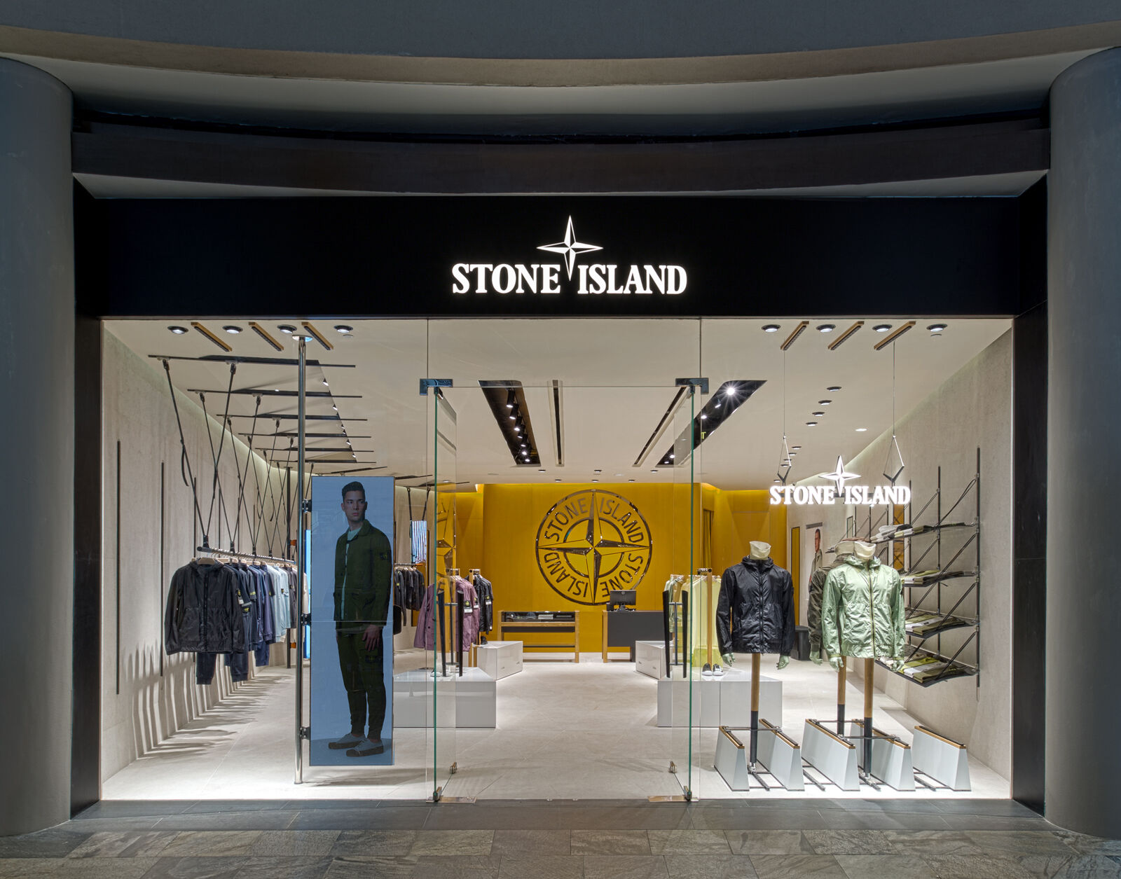 Exterior view of a lit up store with a big glass window, glass entrance doors in the center and a back lit Stone Island logo and compass rose on top of the window.