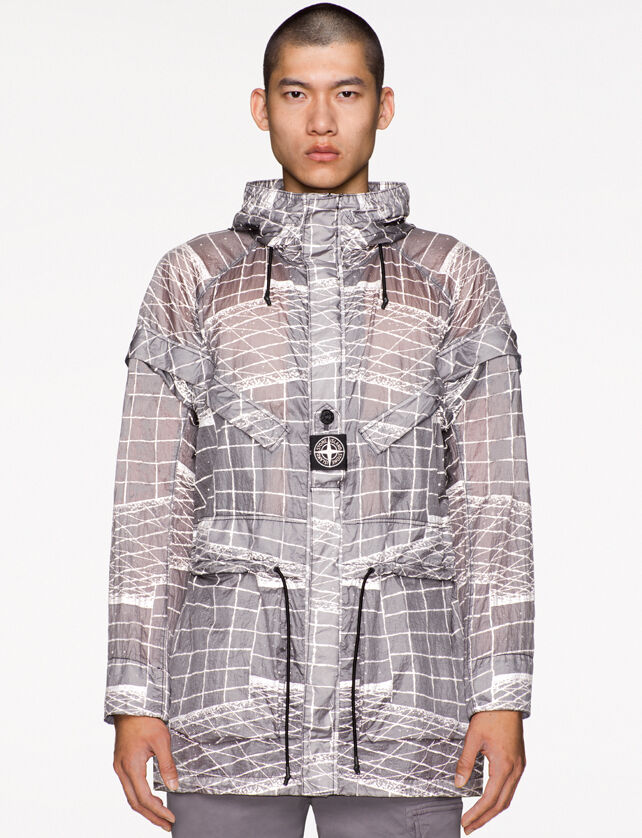 Model wearing gray pants and a light gray see through hooded jacket with a white print, drawstring at waist and a fastening placket with a buttoned central strap on the chest featuring the Stone Island research badge.