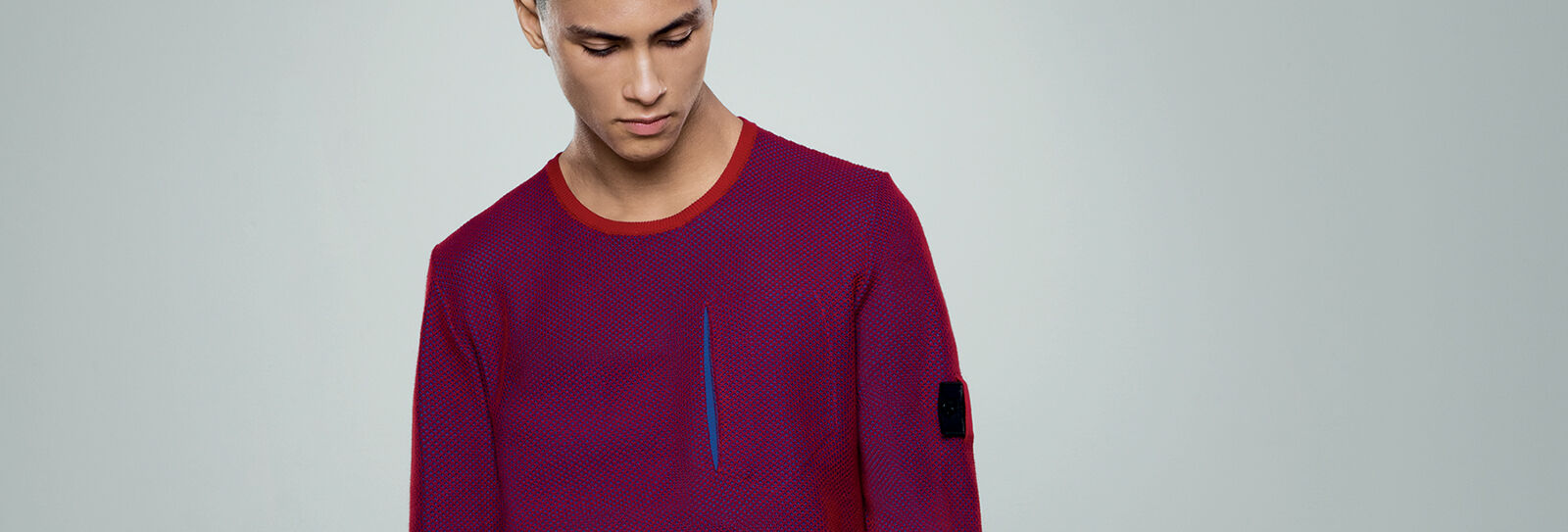Close up shot of model wearing a red and blue crewneck sweater with one standing pocket on the chest and the Stone Island Shadow Project badge on the upper left sleeve.