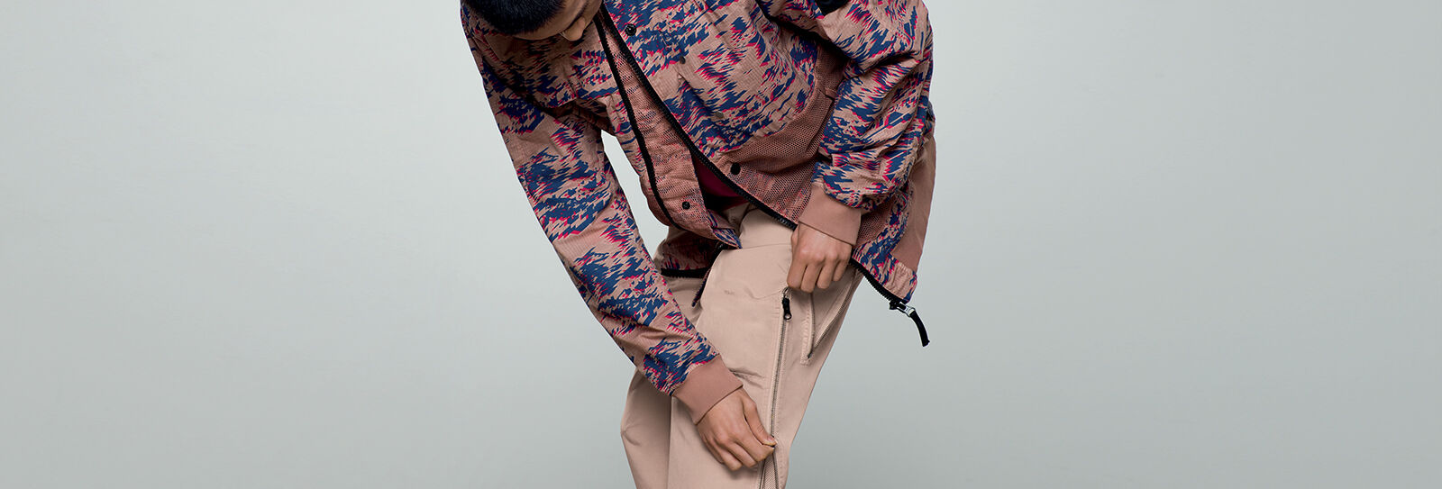 Model wearing a khaki, blue and red print jacket with black zipper fastening and beige pants with a two ways zipper on the left leg.
