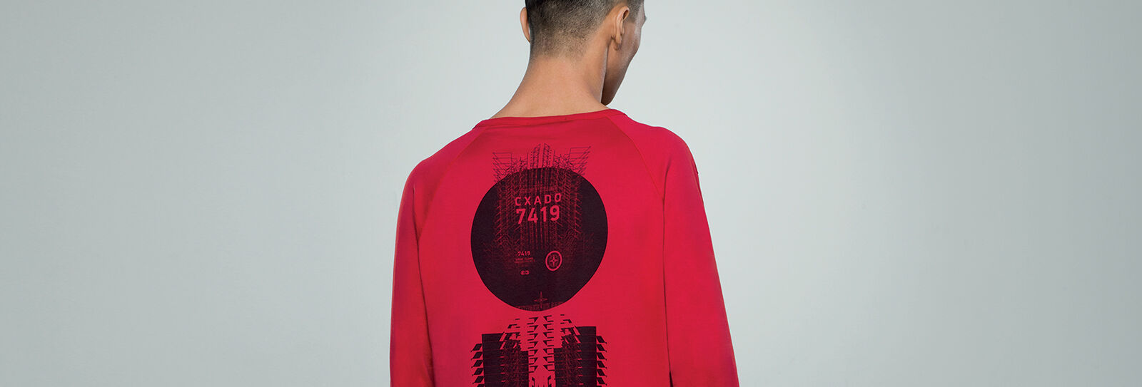 Model showing the back of a red crewneck t shirt with long raglan sleeves and a black graphic print with a compass rose and lettering that reads CXADO 7419.