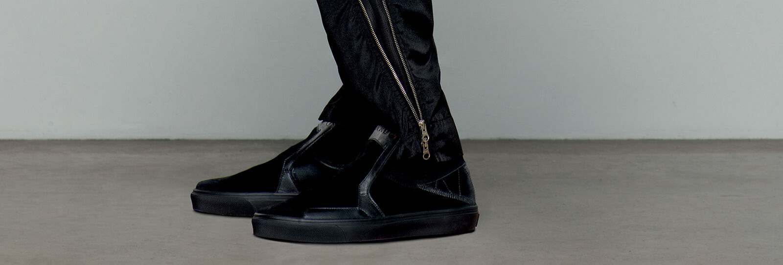 Close up shot of model wearing black pants with golden two ways zipper and a pair of black lace less shoes.