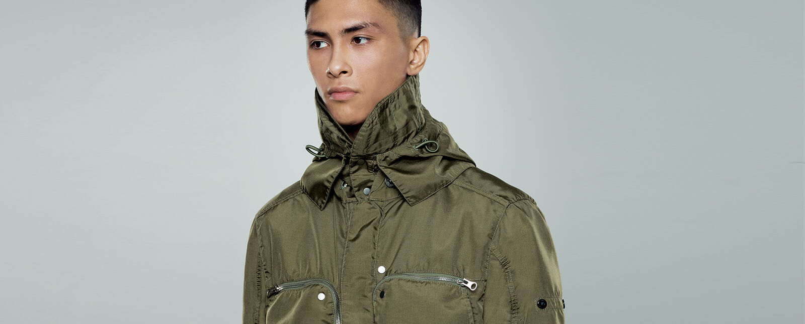 Close up shot of model wearing a military green jacket with standing collar with drawstring and two chest pockets with zipper fastening.
