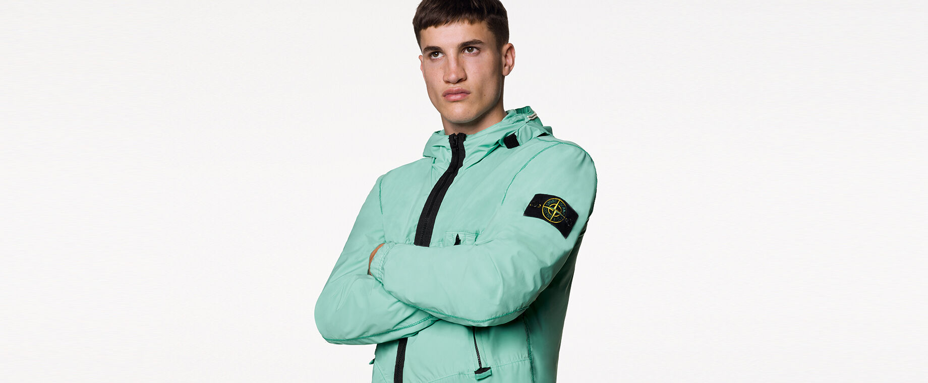 Model wearing a mint green light jacket with hood, black zipper fastening and the Stone Island badge on the upper left sleeve.