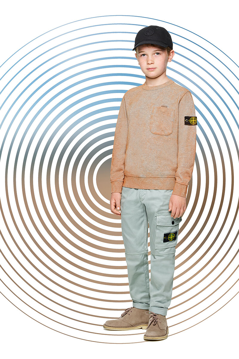 Junior model against a multicolor spiral backdrop, wearing khaki cargo pants, an orange crewneck sweatshirt with one chest pocket and a black cap with a black Stone Island compass rose logo.