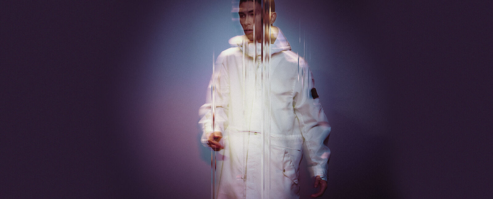 View of a model wearing a white parka with Stone Island Shadow Project badge on the upper left sleeve.