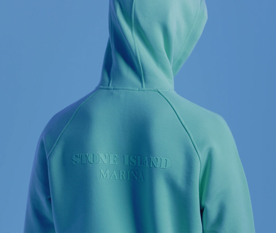Close up shot of model showing the back of an aqua green hooded sweatshirt with lettering that reads STONE ISLAND MARINA.