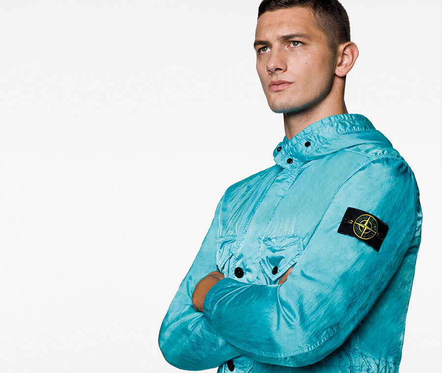 Model wearing a light blue shiny effect jacket with hood, button fastening, two bellows chest patch pockets with a triangular flap and snap, drawstring at waist and the Stone Island badge on the upper left sleeve.