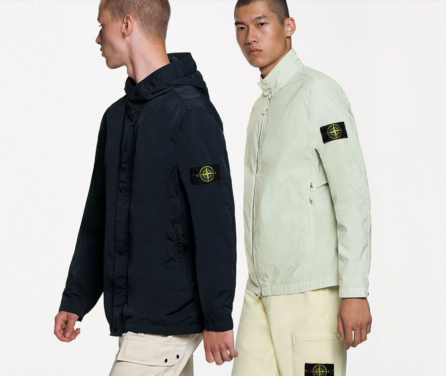 Two models, one wearing off white cargo pants and a hooded dark colored jacket, the other one wearing light yellow cargo pants and a light mint green jacket with standing collar.