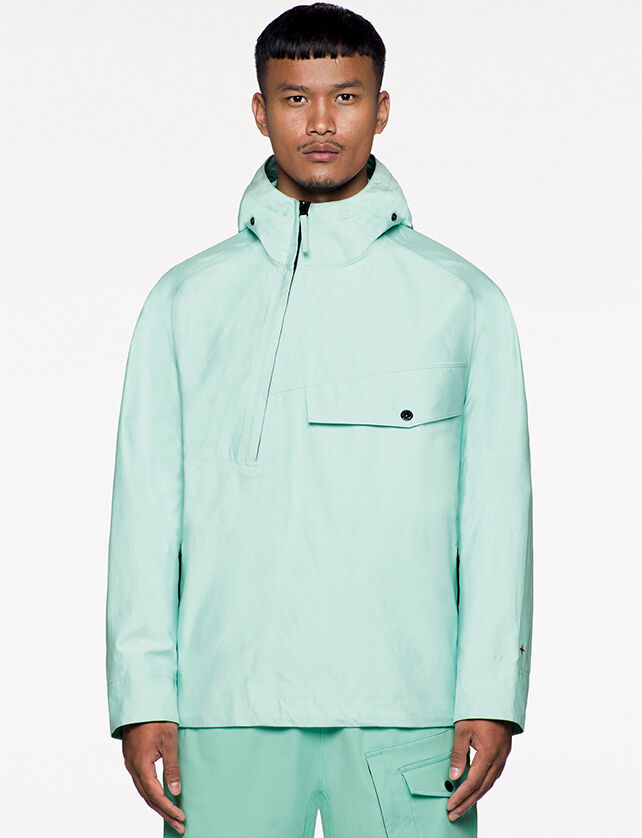 Model wearing aqua green cargo pants and a matching jacket with hood, an asymmetrical half zipper fastening, a chest pocket with flap and snap and the Stone Island little star in red on the left cuff.