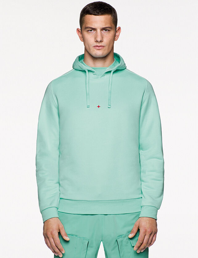 Model wearing aqua green cargo pants and a matching sweatshirt with hood and the embroidery of the Stone Island little star in red on the chest.