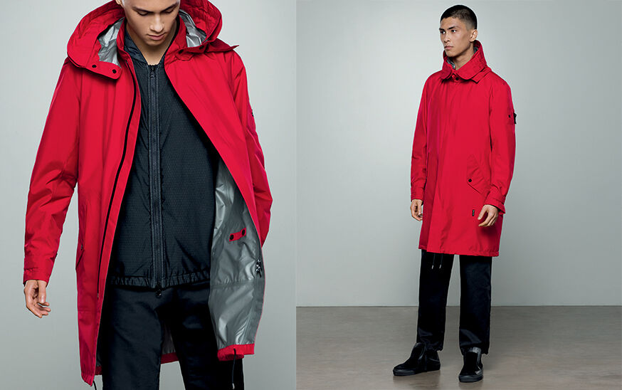 Two shots of the same model, one close up and one full body, showing dark colored pants, a matching jacket with zipper fastening and a bright red parka with hood, standing collar, black zipper fastening and strap at cuffs.