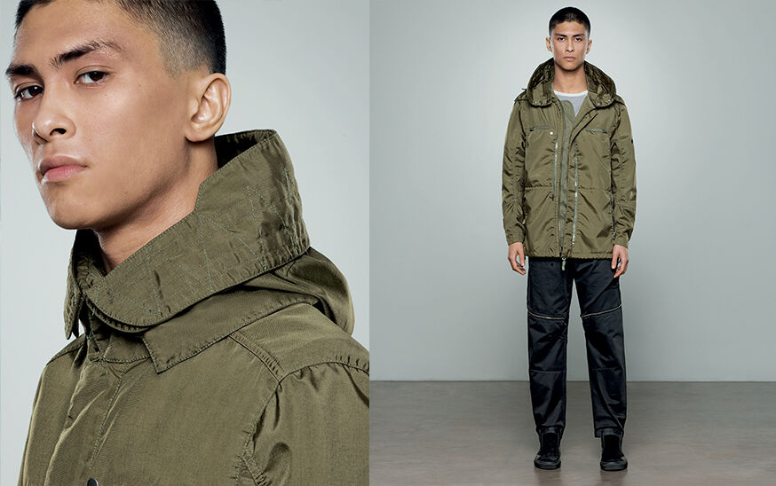 Two shots of the same model, one close up and one full body, showing dark colored pants with zipper details and a military green jacket with standing collar and two chest pockets with zipper fastening.