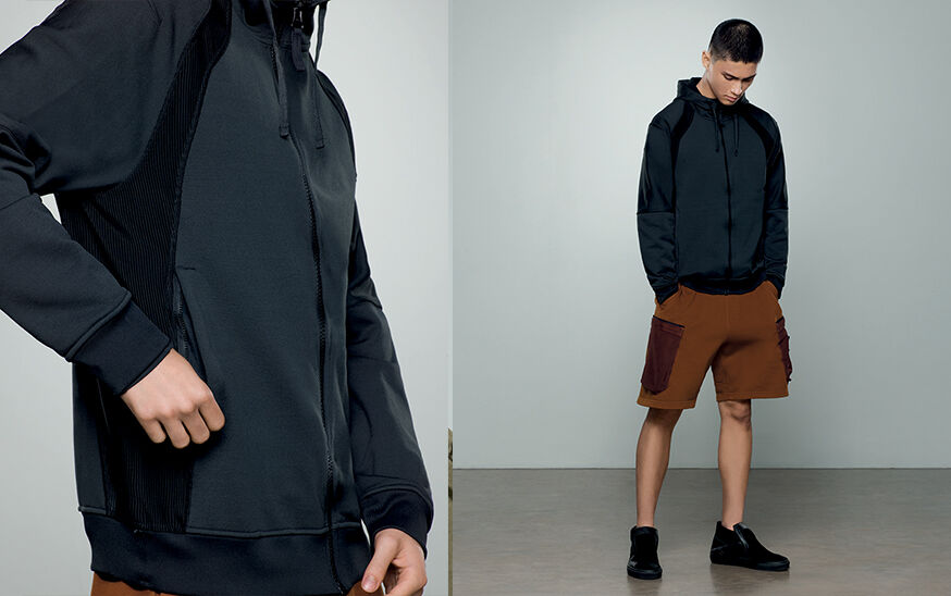 Two shots of the same model, one close up and one full body, showing a dark colored sweatshirt with hood, zipper fastening and brown cargo shorts with ribbed patch pockets.