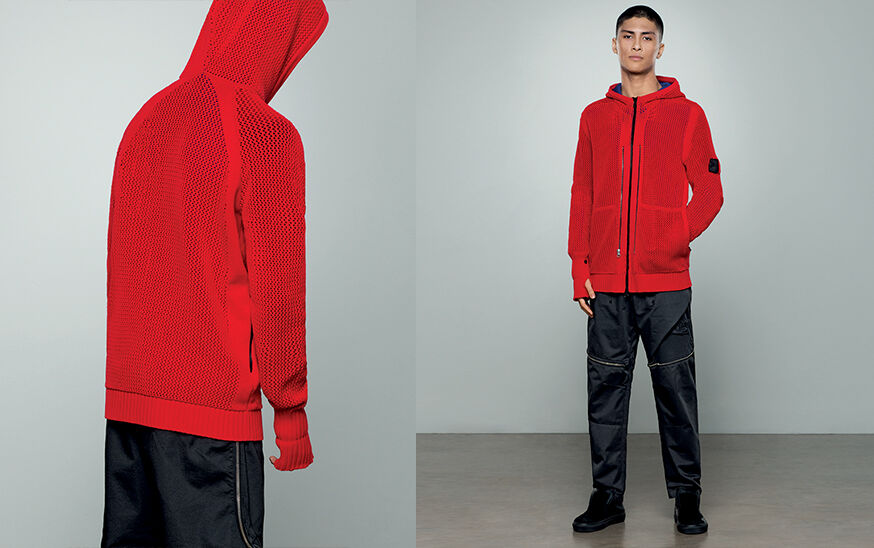 Two shots of the same model, showing the back close up and the front full body, wearing dark colored pants with zipper details and a bright red sweater with hood and zipper fastening.