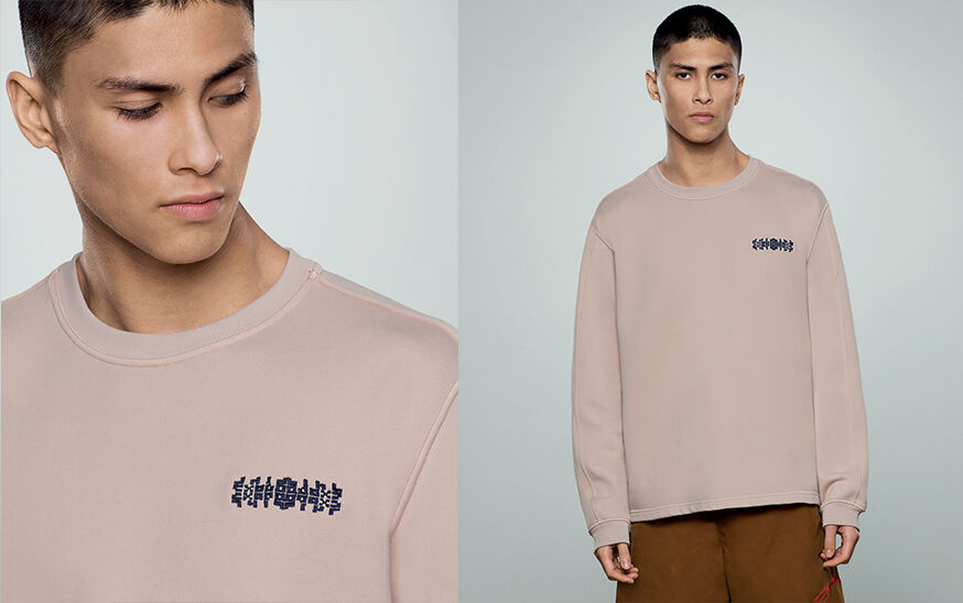 Two shots of the same model, one close up of the chest embroidery and one close up, wearing tan pants and a beige crewneck sweatshirt with long sleeves.