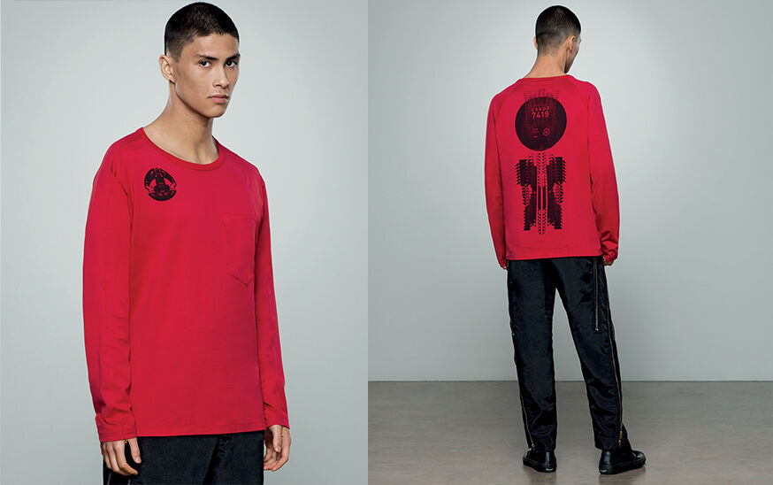 Two shots of the same model, showing the front close up and the back full body, wearing dark colored pants with zipper details and a red crewneck t shirt with long sleeves, a breast pocket and a black graphic print on the chest and back.