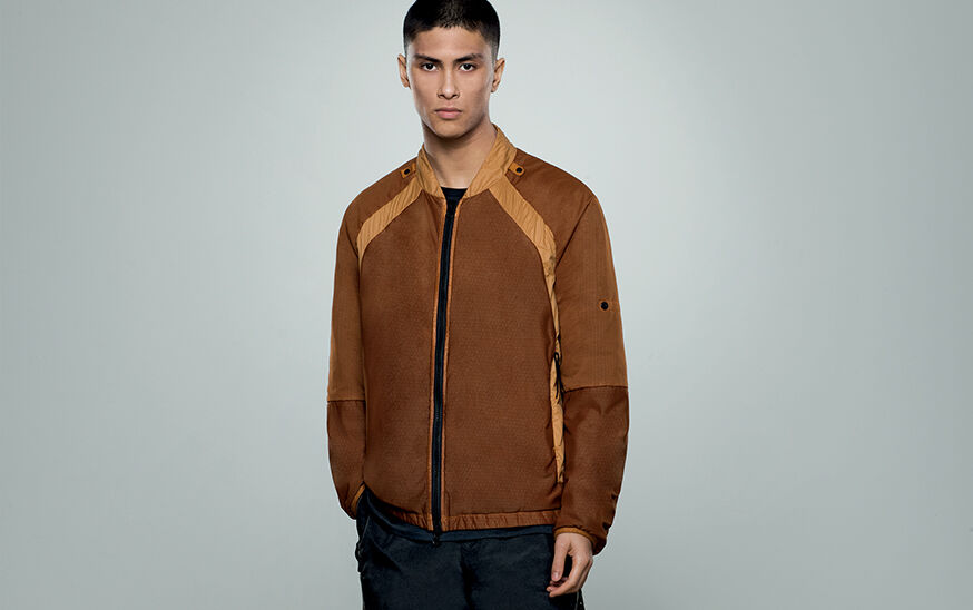 Model wearing dark colored pants and a tan bomber jacket with beige details and black zipper fastening.
