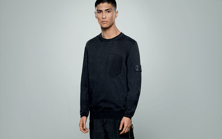 Model wearing dark colored pants and a matching crewneck sweatshirt with a breast pocket and the Stone Island Shadow Project badge on the upper left sleeve.
