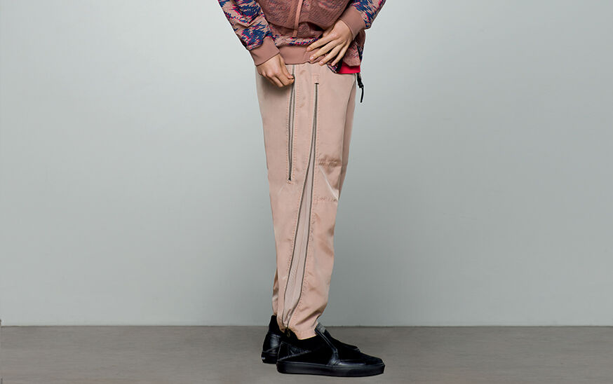 Close up shot of model wearing black lace less shoes, beige pants with zippers on the side and a khaki, blue and red print jacket.